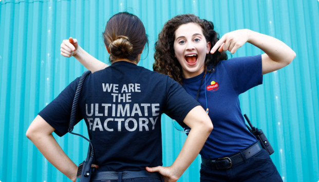 A woman pointing to another woman's back where it's written: We are the ultimate factory